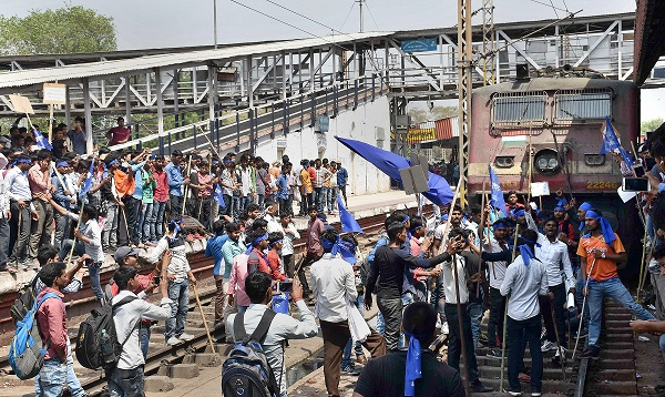 India Tv -   Gaya: Dalit community members stop a train at Gaya railway station during 'Bharat Bandh' call given by Dalit organisations against the alleged 'dilution' of the Scheduled Castes/Scheduled Tribes act, in Gaya on Monday.