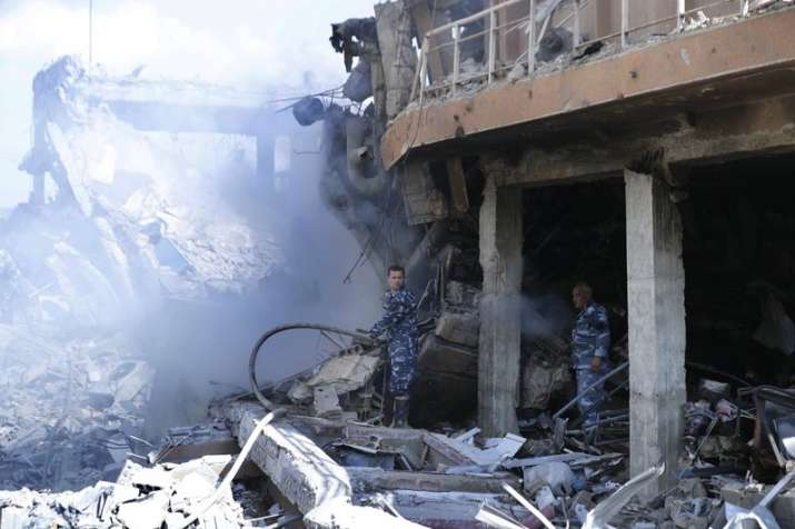 India Tv - Firefighrers extinguish smoke that rises from the damage of the Syrian Scientific Research Center which was attacked by US, British and French military strikes to punish President Bashar Assad for suspected chemical attack against civilians, in Barzeh, near Damascus, Syria, Saturday, April 14, 2018.
