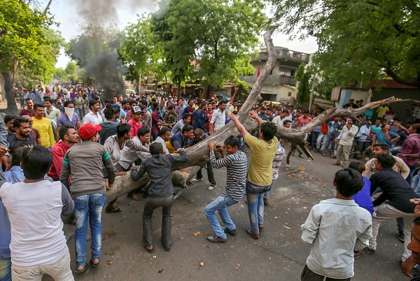 India Tv - Ahmedabad: Members of Dalit community block a road wuth a tree as they stage a protest during 'Bharat Bandh' against the alleged 'dilution' of Scheduled Castes/Scheduled Tribes act, in Ahmedabad on Monday.