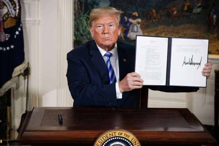 India Tv - President Donald Trump shows a signed Presidential Memorandum after delivering a statement on the Iran nuclear deal from the Diplomatic Reception Room of the White House, Tuesday, May 8, 2018, in Washington.