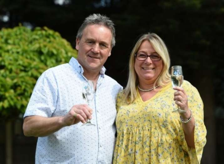 Lottery winners mow celebratory champagne bottle and