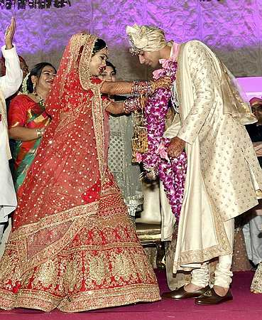 India Tv - A stage was put up at the college ground where the groom dressed in pink sherwani and pyjama of matching shade exchanged garlands with the bride who wore a bright red dress.