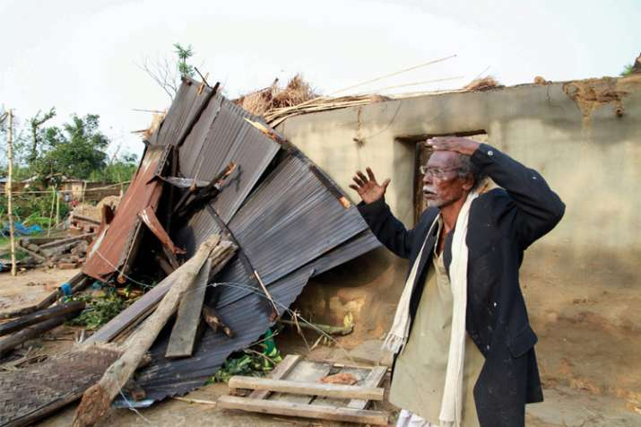 A man reacts near his damaged house after a cyclone hit