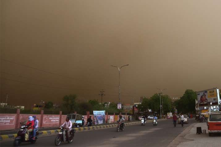India Tv - Bikaner: Vehicle ride past on a road during a dust storm in Bikaner on Wednesday.