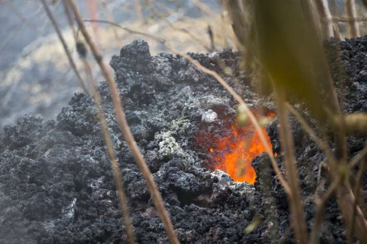 India Tv - Lava glows from a vent on a lava bed at the Leilani Estates, Saturday, May 5, 2018, in Pahoa, Hawaii. The Hawaiian Volcanoes Observatory said eight volcanic vents opened in the Big Island residential neighborhood of Leilani Estates since Thursday.