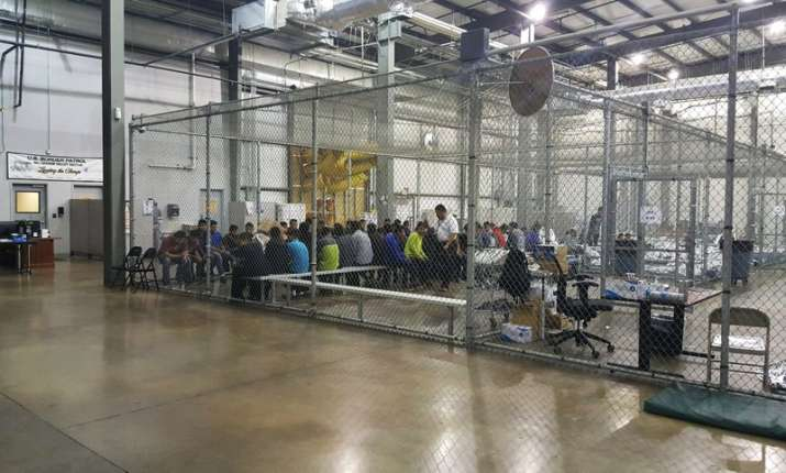 India Tv - In this photo provided by U.S. Customs and Border Protection, people who've been taken into custody related to cases of illegal entry into the United States, sit in one of the cages at a facility in McAllen, Texas, Sunday, June 17, 2018.