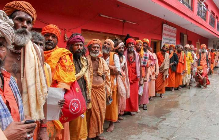 Sadhus wait in a queue to get themselves registered for
