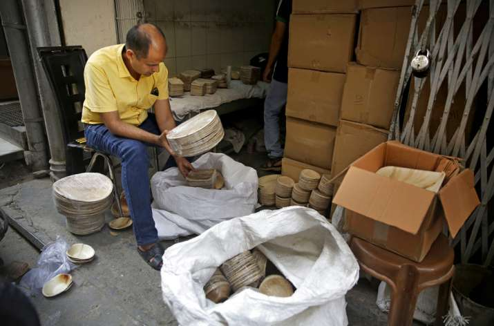 India Tv - Sanjay Aggarwal inspects the products he purchased from Prakritii, or nature, a company that manufactures eco-friendly dinnerware at the company's warehouse in New Delhi.