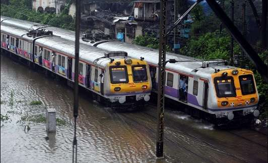 India Tv - Suburban trains chug on water-logged tracks during heavy rains in Mumbai