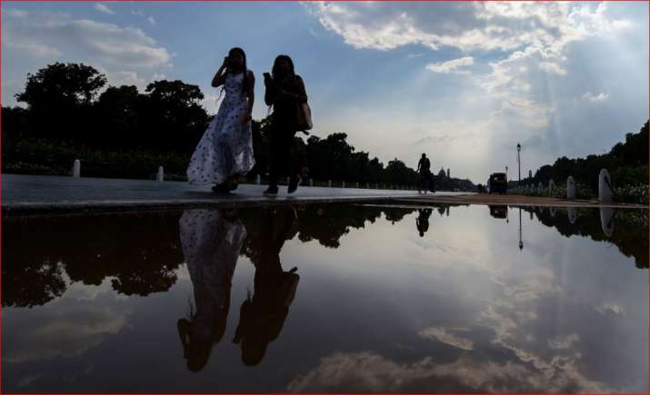 Women walk past a puddle of water at Rajpath in New Delhi