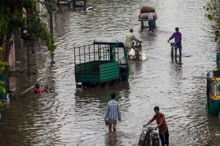 India Tv - People move through a flooded street after heavy rains, in Ahmedabad on Sunday, June 24.