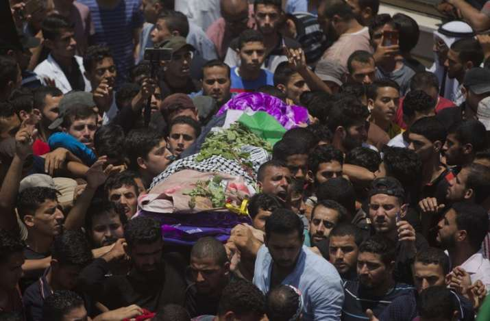 Palestinian mourners carry the body of a volunteer