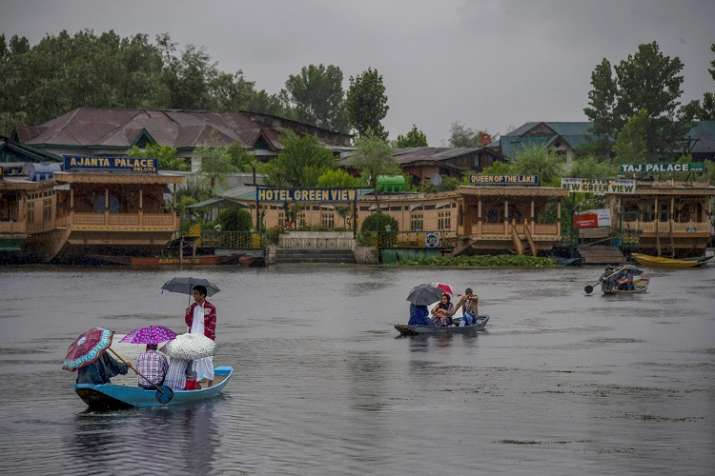 India Tv - People travel in a boat to cross Dal Lake during heavy rainfall, in Srinagar on Friday, June 29.