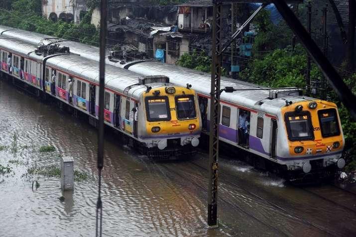 India Tv - Suburban trains chug on water-logged tracks during heavy rains, in Mumbai on Monday.