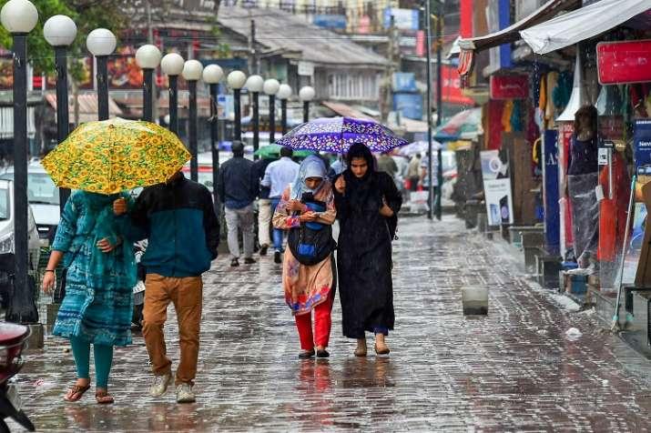India Tv - Pedestrians walk with umbrellas during heavy rains in Srinagar on Friday, June 29.