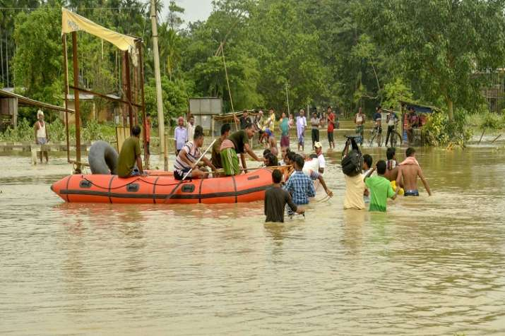Tripura State Rifles personnel travel on a boat through a