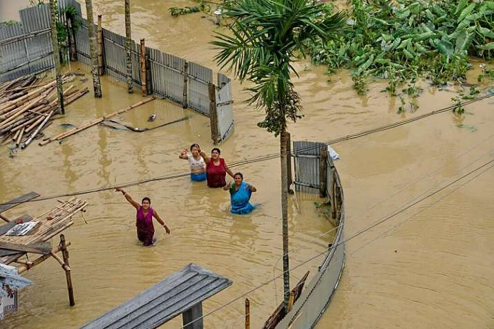 India Tv - Villagers wave to the helicopter supplying food and other essentials in the flood-affected Kailashahar town in Unakoti district of Tripura on Friday.