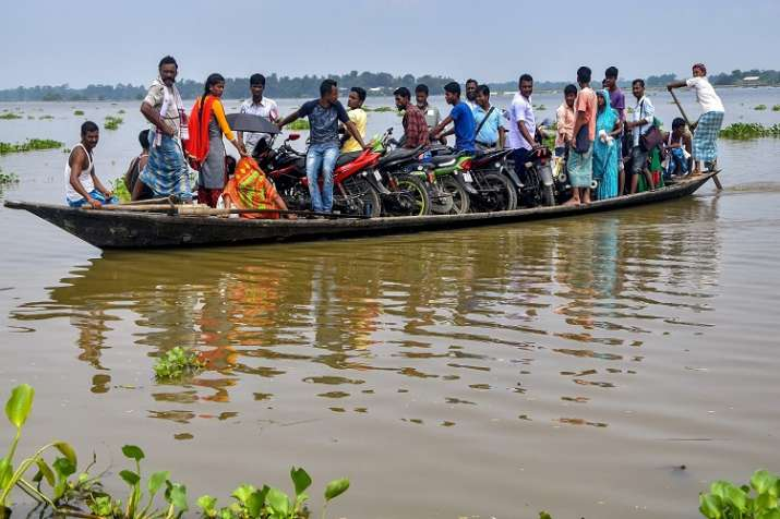 India Tv - Flood affected people use a boat to commute at Ashigarh village, in Morigaon district of Assam on Saturday.