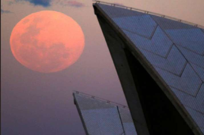 India Tv - A supermoon rises behind the roof of the Sydney Opera House.