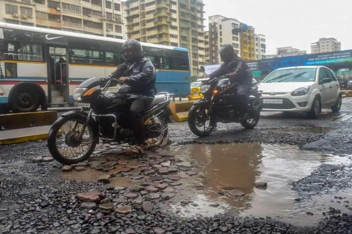 Commuters ride past pot-holes filled road after heavy