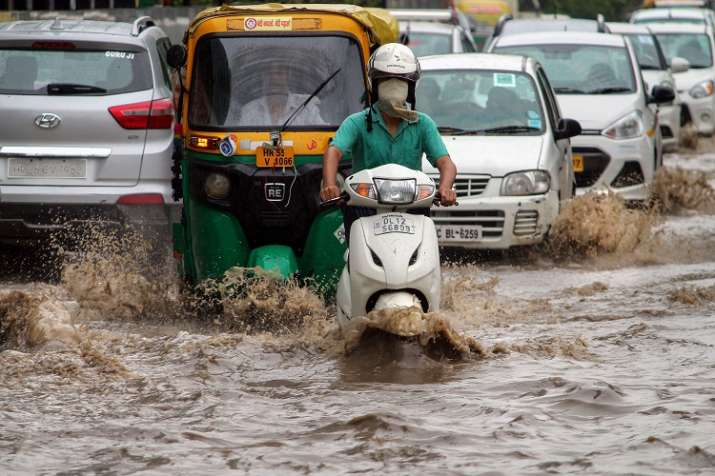 India Tv - Commuters wade through water-logged road in Gurgaon as heavy rains continue to batter Delhi-NCR. (Photo/PTI)