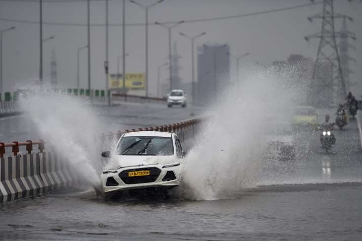 India Tv - A car wades through a waterlogged road on NH-24  in New Delhi, on Thursday, July 26, 2018. (Photo/PTI Ravi Choudhary)