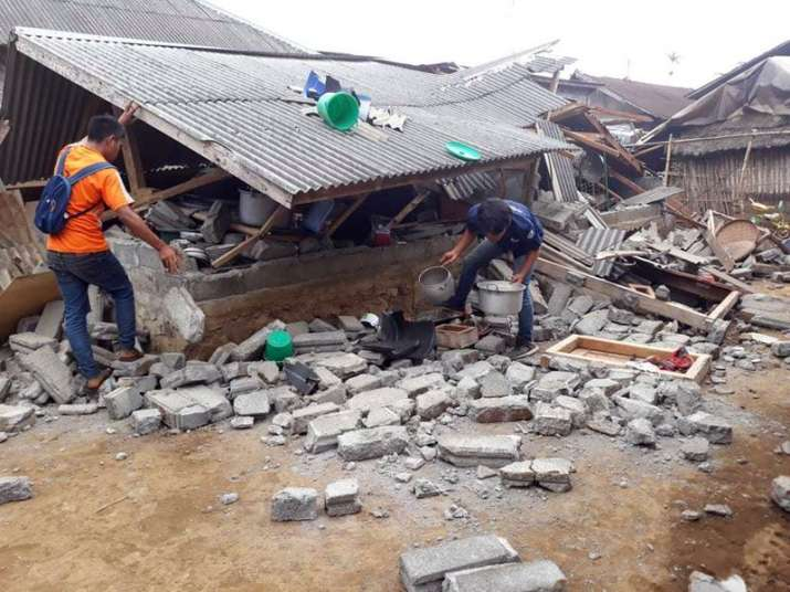 Villagers clear debris caused by an earthquake at Sajang