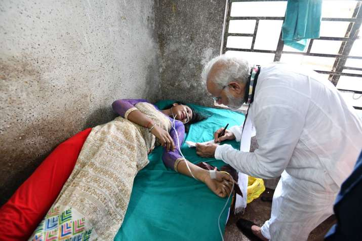 PM Modi talking to a woman injured after a tent fell during