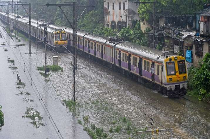 India Tv - Local trains chug on the flooded railway tracks during rains, in Mumbai on Tuesday.