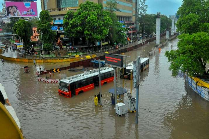 India Tv - City buses stuck at a flooded road after heavy rains, in Nagpur on Friday.
