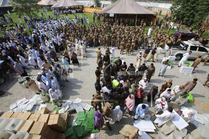 India Tv - Election staff gather at a distribution center to receive polling material for elections, in Peshawar, Pakistan, Tuesday, July 24, 2018. (AP Photo/Muhammad Sajjad)