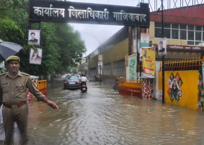 India Tv - Ghaziabad: Commuters wade through a waterlogged street after monsoon rainfall, at District Magistrate office