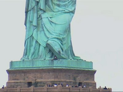 India Tv - Several people who hung a banner calling for abolishing Immigration and Customs Enforcement from the Statue of Liberty's pedestal on the Fourth of July have been arrested, and authorities say a person is scaling the statue's base. (July 4)
