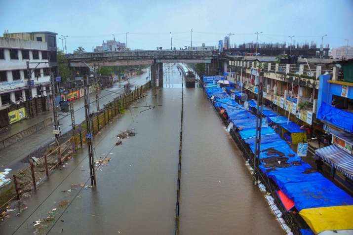 India Tv - A suburban train wades through water-clogged railway tracks after heavy rainfall, in Nalasopara station on Tuesday.