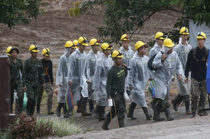 India Tv - Rescuers walk toward the entrance to a cave complex where five were still trapped, in Mae Sai, Chiang Rai province.