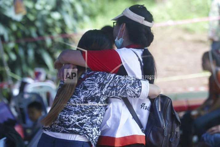India Tv - A family member, left, and a Thai official hug each other near a cave where 12 boys and their soccer coach are trapped, in Mae Sai, Chiang Rai province, in northern Thailand. (Photo/AP Photo/Sakchai Lalit)