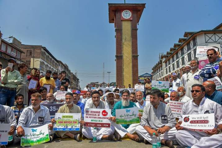 India Tv - Kashmiri traders hold placards and raise slogans during a sit-in protest against the petitions in the Supreme court challenging the validity of Article 35A.