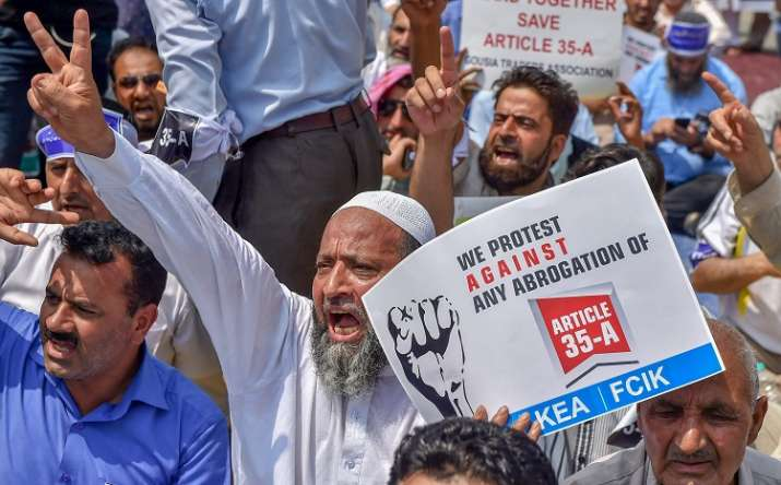 India Tv - Srinagar: Kashmiri traders hold placards and raise slogans during a sit-in protest against the petitions in the Supreme Court challenging the validity of Article 35A, in Srinagar on Sunday, August 05, 2018.
