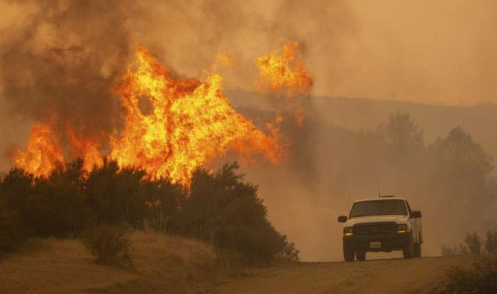India Tv - A truck passes by flames during the Ranch Fire in Clearlake Oaks, California, on Sunday,