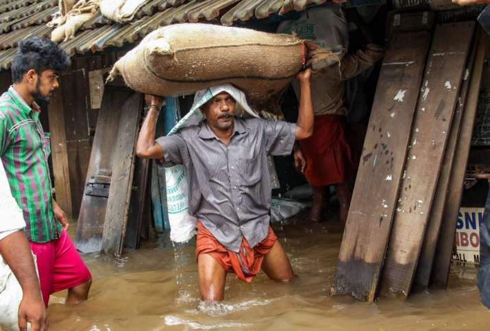 India Tv - Kozhikode: A person carries a grain sack as his house gets flooded after Kakkayam dam was opened following heavy monsoon rainfall, in Kozhikode on Thursday, Aug 16, 2018.