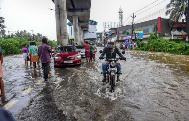 India Tv - Kochi: People wade across a waterlogged street at a flood-affected region following heavy monsoon rainfall, in Kochi on Thursday, Aug 16, 2018.