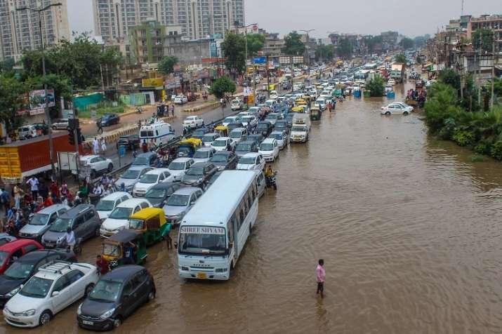 Vehicle wade through a waterlogged road at Subhash Chowk