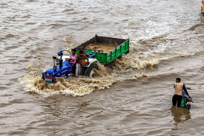 India Tv - A tractor wades through a waterlogged road after heavy rains in Gurugram on Tuesday.