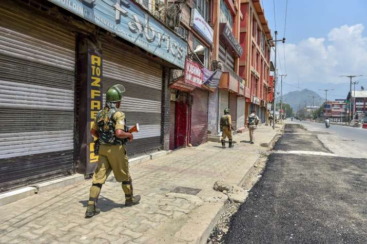 India Tv - Srinagar: Security personnel patrol a street during a two-day strike called by the separatist leaders against the petitions in the Supreme court challenging the validity of Article 35A, in Srinagar on Sunday