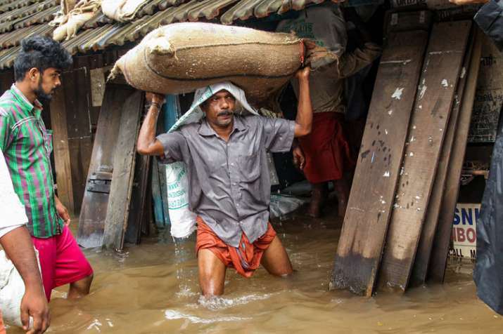 A person carries a grain sack as his house gets flooded
