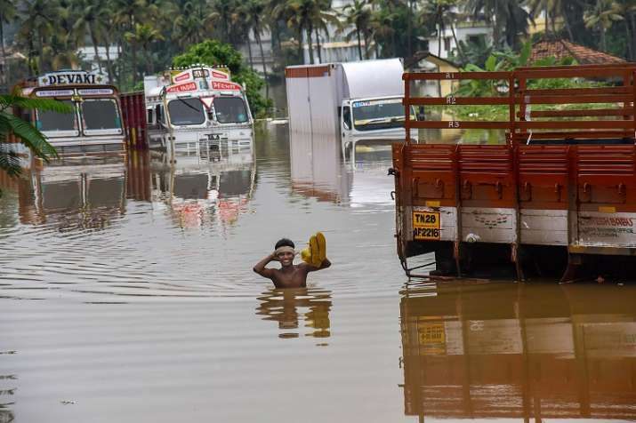 India Tv - A person stands near submerged trucks on a waterlogged street in Kochi (PTI Photo)