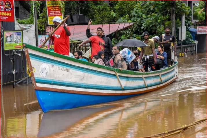 India Tv - Rescue workers row a boat carrying locals who were stranded in floods following heavy monsoon rainfall, in Kochi