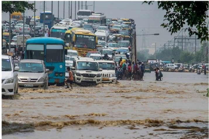 India Tv - Vehicle wade through a waterlogged road at Subhash Chowk after heavy rains in Gurugram.