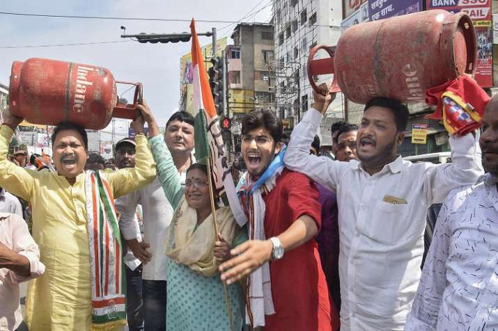 Congress Party workers raise slogans holding LPG cylinders