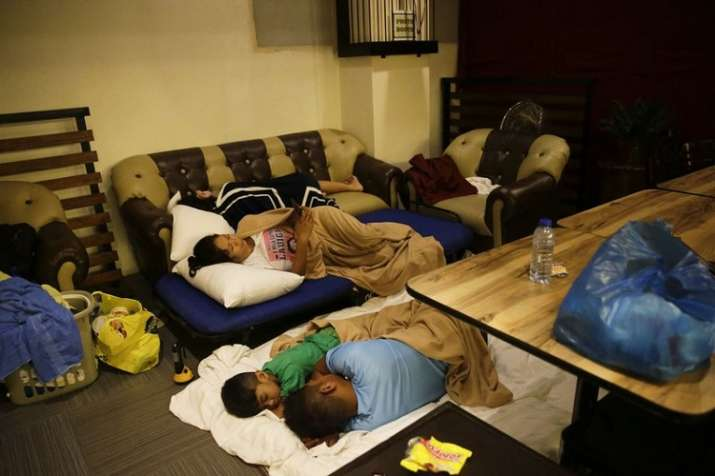 India Tv - Guests sleep inside a hotel restaurant after the roof of their room was partly damaged due to strong winds from Typhoon Mangkut.